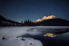 高积雪的山,在与一个半结冰的湖的满月光在夜空下充分星,班夫国家公园,加拿大 免版税图库摄影