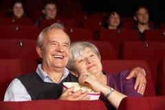 高级在戏院的夫妇注意的影片 免版税库存图片