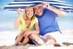 高级夫妇在沙滩伞下 免版税库存照片
