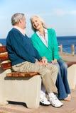 高级夫妇坐长凳Sea Together 免版税图库摄影