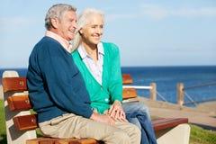 高级夫妇坐长凳Sea Together 图库摄影