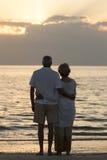 高级夫妇拥抱日落热带海滩 免版税库存图片