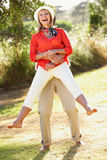 高级夫妇获得乐趣一起在庭院 免版税库存照片