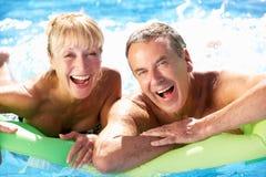 高级夫妇获得乐趣在游泳池 免版税库存照片