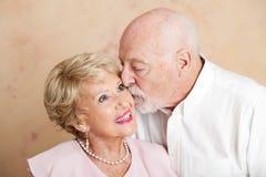 高级夫妇-在面颊的亲吻 免版税库存图片