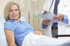 高级女性妇女患者在医院病床上 免版税库存图片