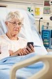 高级女性患者在使用移动电话的医院病床上 免版税库存图片