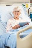 高级女性耐心放松在医院病床上 免版税库存图片