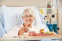 高级女性耐心的吃膳食在医院病床上 免版税图库摄影