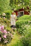 高级妇女在庭院里 免版税库存图片