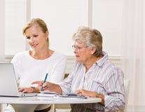 高级妇女文字检查在女儿帮助下 库存图片