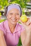 高级嬉戏妇女微笑吃室外的苹果 免版税图库摄影