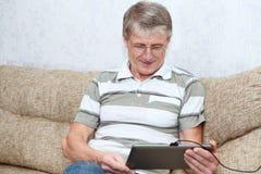 高级成人人感兴趣与片剂计算机 免版税库存照片