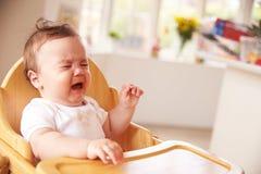 高脚椅子的不快乐的婴孩在膳食时间 免版税库存照片