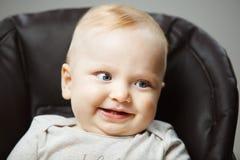 高脚椅子的婴孩有感兴趣的神色和开朗的笑的 免版税库存图片
