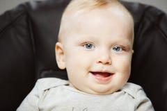 高脚椅子的婴孩有感兴趣的神色和开朗的笑的 免版税图库摄影