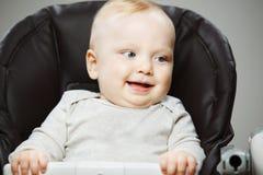 高脚椅子的婴孩有感兴趣的神色和开朗的笑的 库存照片