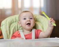 高脚椅子的愉快的婴孩与匙子在他的手上 库存图片