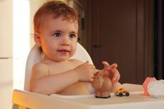 高脚椅子的愉快的微笑的婴孩 库存照片