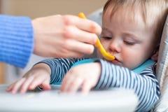 高脚椅子的挑剔男婴拒绝食物在吃饭时间 免版税库存照片