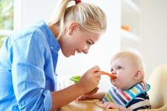 高脚椅子的母亲哺养的男婴 免版税库存图片
