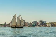高船在有街市哈利法克斯地平线的港口在sunn 免版税库存图片