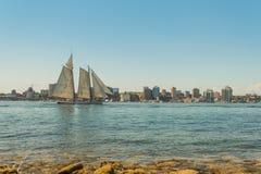 高船在有街市哈利法克斯地平线的港口在sunn 免版税库存照片