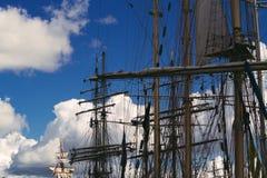 高船帆柱和索具现出轮廓反对剧烈的天空在日落 免版税库存照片