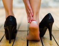 高跟鞋有时伤害,在脚腕的一点白斑 在木地板上的黑高跟鞋 免版税库存图片