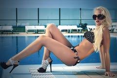 高跟鞋的白肤金发的性感的妇女 太阳镜的美丽的白肤金发的妇女在游泳池附近 比基尼泳装的夏天女孩 免版税库存照片