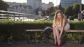 高跟鞋的迷人的妇女按摩疲乏的腿的 股票录像