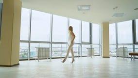 高跟鞋的迷人的白肤金发的妇女走和转动在空的办公室的 股票视频