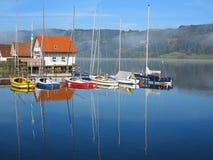 高跷房子和帆船在湖风景 免版税库存图片