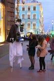 高跷的一个街道执行者在圣彼得招待游人 免版税库存图片