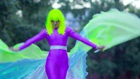 高跷的女孩在街道上的紫罗兰色衣物舞蹈 影视素材