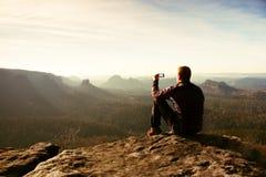 高远足者由在山峰顶的巧妙的电话拍照片在日出 免版税库存照片