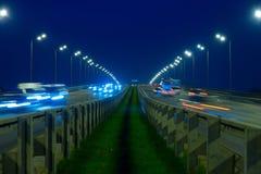 高速公路交通汽车在blured的晚上 继续前进在bri的汽车路 免版税库存图片