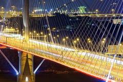 高速公路桥梁在与轻的交通踪影的晚上  库存图片
