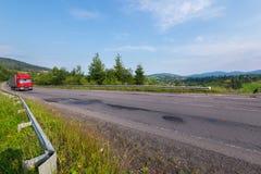 高速公路用在绿色冷杉背景的栏杆装备,一辆红色卡车乘坐 免版税库存图片