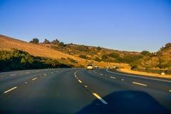 高速公路绕通过在日落的小山 库存照片