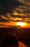高速公路路和汽车在橙色日落天空前面在冬天 免版税库存照片