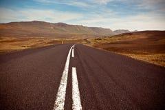 高速公路通过在一个蓝色总和之下的干燥石渣熔岩荒野风景 库存照片