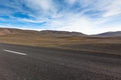 高速公路通过在一个蓝色总和之下的干燥石渣熔岩荒野风景 免版税库存图片