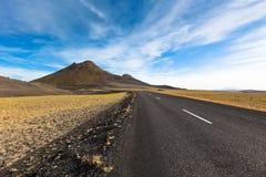 高速公路通过石渣在一个蓝色夏天之下的熔岩荒野风景 免版税库存图片
