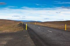 高速公路通过石渣在一个蓝色夏天之下的熔岩荒野风景 库存图片