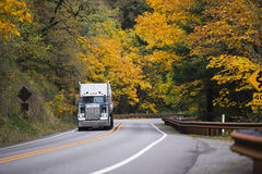 绕高速公路黄色秋天的大半船具卡车拖车 免版税库存照片