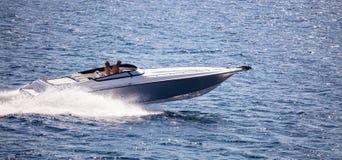 高速小船在风平浪静快速地进来 人们享受夏天体育 免版税库存图片