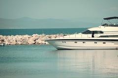高速小船,豪华游艇在船坞在海,在背景的蓝天 白色豪华游艇,海军陆战队员滑动海表面上 免版税图库摄影