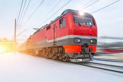 高速红色活动旅客列车在冬天高速乘坐在多雪的风景附近 免版税库存图片