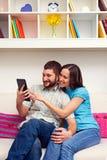 兴高采烈的夫妇坐沙发 图库摄影